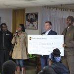 Mama Darlene Graham presents a check to Ile Omode.
